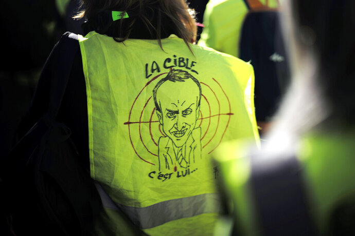 FILE - In this Feb.23, 2019 file photo, a protester wears a a yellow vest with a drawing depicting French President Emmanuel Macron and the word