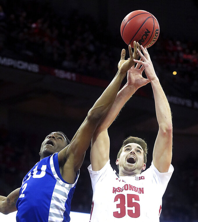 Wisconsin forward Nate Reuvers (35) and Eastern Illinois forward Jordan Skipper-Brown (2) reach for a rebound during the first half of an NCAA college basketball game in Madison, Wis., Friday, Nov. 8, 2019. (John Hart/Wisconsin State Journal via AP)