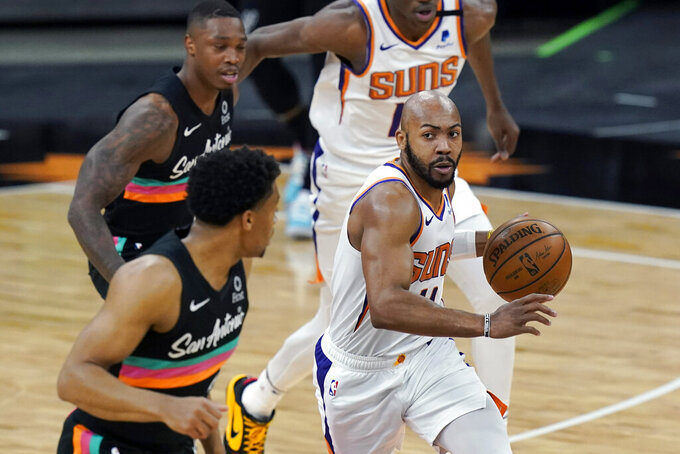 FILE - In this May 16, 2021, file photo, Phoenix Suns guard Jevon Carter (4) drives around San Antonio Spurs forward Keldon Johnson, left, during the first half of an NBA basketball game in San Antonio. The Brooklyn Nets acquired backup guard Jevon Carter and the draft rights to center Day'Ron Sharpe from the Phoenix Suns for guard Landry Shamet, the teams announced Friday, Aug. 6, 2021. (AP Photo/Eric Gay, File)