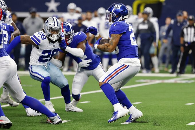 FILE - In this Sunday, Oct. 10, 2021, file photo, New York Giants running back Saquon Barkley (26) carries the ball as Dallas Cowboys safety Malik Hooker (28) rushes in during the first half of an NFL football game in Arlington, Texas. The talented fourth-year running back is probably going to miss at least a game or two after spraining his left ankle on a fluke play early in the Giants 44-20 loss to the Dallas Cowboys on Sunday. (AP Photo/Michael Ainsworth)