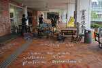 In this Tuesday, Nov. 12, 2019, photo, student protesters walk by the vandalized Hong Kong University as protests continue in Hong Kong. A sharp escalation of violence in Hong Kong has once again raised the question of how China's central government will respond. Experts said national security measures and deployment of the armed forces remain possibilities, though Beijing may just as likely allow destruction to continue unfolding. (AP Photo/Kin Cheung)