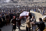 People carry the coffin of a coal mine worker, who along with others was killed by gunmen near the Machh coal field in Quetta, Pakistan, Saturday, Jan. 9, 2021. Hundreds of Pakistani Shiites gathered to bury 11 coal miners from the minority Hazara community who were killed by the Islamic State group, ending over a week of protests that sought to highlight the minority community's plight. (AP Photo/Arshad Butt)