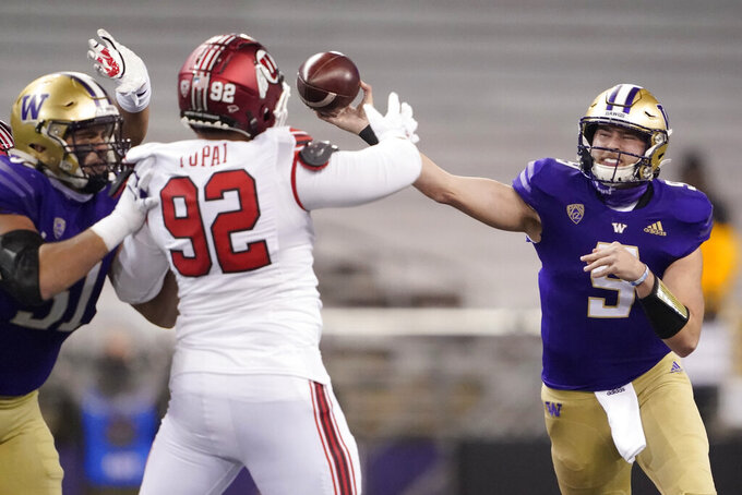Washington quarterback Dylan Morris, right, passes under pressure from Utah defensive end Maxs Tupai (92) during the first half of an NCAA college football game, Saturday, Nov. 28, 2020, in Seattle. (AP Photo/Ted S. Warren)
