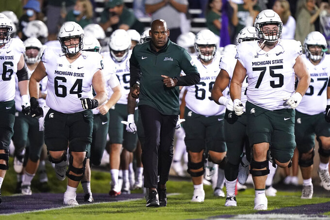Michigan State coach Mel Tucker, center, runs onto the field with the team before an NCAA college football game against Northwestern in Evanston, Ill., Friday, Sept. 3, 2021. (AP Photo/Nam Y. Huh)