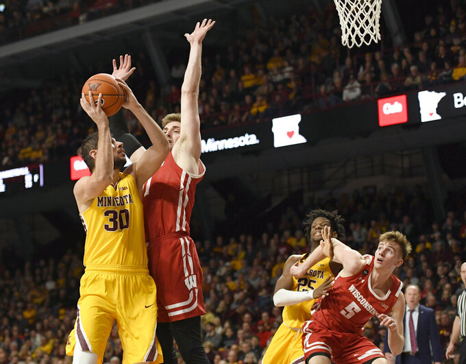 Minnesota's Alihan Demir (30) shoots next to Wisconsin's Micah Potter (11) as Wisconsin's Tyler Wahl (5) blocks out Minnesota's Daniel Oturu (25) during the first half of an NCAA college basketball game Wednesday, Feb. 5, 2020, in Minneapolis. (AP Photo/Hannah Foslien)