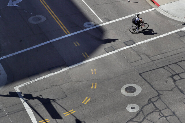 A lone cyclist crosses an empty street in downtown Phoenix Wednesday, April 1, 2020 during the first full day of Arizona Gov. Doug Ducey's stay-at-home order to slow the spread of the new coronavirus. Gov. Ducey is urging Arizonans to be understanding and reasonable as people and businesses face April 1 due dates for bills such as mortgages, rent, utilities and internet service since the COVID-19 coronavirus outbreak has slowed the economy. The new coronavirus causes mild or moderate symptoms for most people, but for some, especially older adults and people with existing health problems, it can cause more severe illness or death. (AP Photo/Matt York)