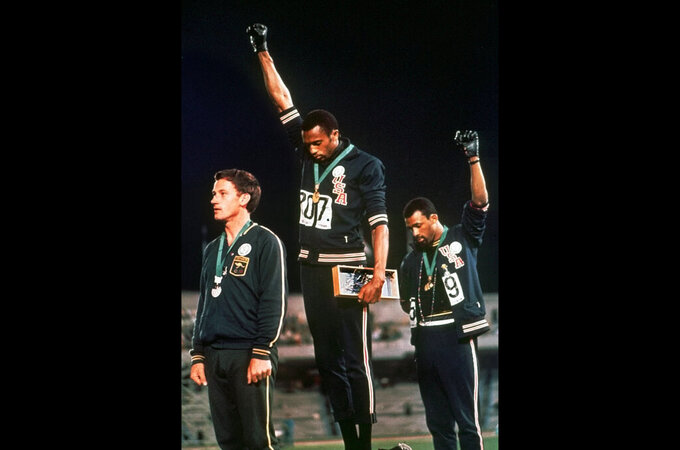 "FILE - In this Oct. 16, 1968 file photo, U.S. athletes Tommie Smith, center, and John Carlos raise their gloved fists after Smith received the gold and Carlos the bronze for the 200 meter run at the Summer Olympic Games in Mexico City. Athletes who make political or social justice protest at the Tokyo Olympics were promised legal support Thursday April 22, 2021, by a global union and an activist group in Germany. The pledges came one day after the International Olympic Committee confirmed its long-standing ban on ""demonstration or political, religious or racial propaganda"" on the field of play, medal podiums or official ceremonies. (AP Photo/File)"