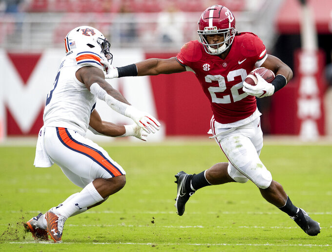 Alabama running back Najee Harris (22) stiff-arms Auburn linebacker Owen Pappoe (0) during an NCAA college football game Saturday, Nov. 28, 2020, in Tuscaloosa, Ala. (Mickey Welsh/The Montgomery Advertiser via AP)