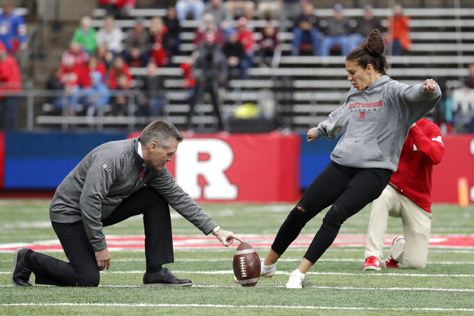 Carli Lloyd, right, of the United States women's national soccer team, kicks a field goal, with Rutgers athletic director Patrick Hobbs holding, during a television timeout in the first half of an NCAA college football game between Rutgers and Northwestern, Saturday, Oct. 20, 2018, in Piscataway, N.J. (AP Photo/Julio Cortez)