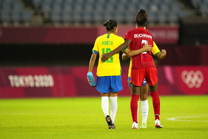 Canada's Kadeisha Buchanan, right, embraces Brazil's Marta at the end of a women's quarterfinal soccer match at the 2020 Summer Olympics, Friday, July 30, 2021, in Rifu, Japan. Canada won 4-3 in a penalty shootout. (AP Photo/Andre Penner)
