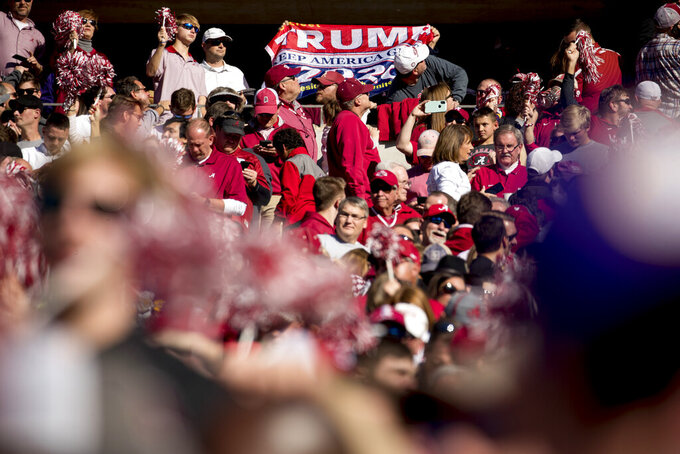 A member of the audience holds up a pro-Trump flag as President Donald Trump and first lady Melania Trump attend a NCAA college football game between LSU and Alabama at Bryant-Denny Stadium, in Tuscaloosa, Ala., Saturday, Nov. 9, 2019. (AP Photo/Andrew Harnik)
