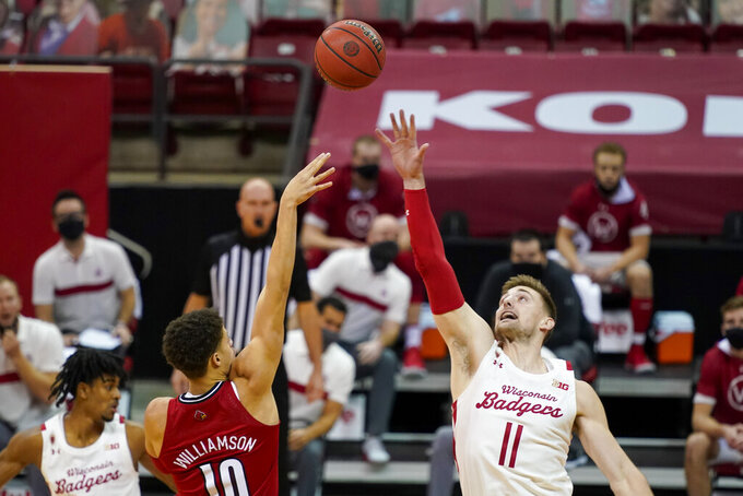 Louisville's Samuell Williamson (10) shoots over Wisconsin's Micah Potter (11) during the first half of an NCAA college basketball game, Saturday, Dec. 19, 2020, in Madison, Wis. (AP Photo/Andy Manis)