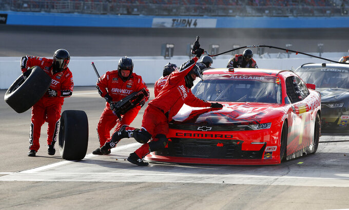 The pit crew for Justin Allgaier (7) scramble around the car to change tires as he makes a pit stop during the NASCAR Xfinity Series auto race at Phoenix Raceway, Saturday, Nov. 7, 2020, in Avondale, Ariz. (AP Photo/Ralph Freso)