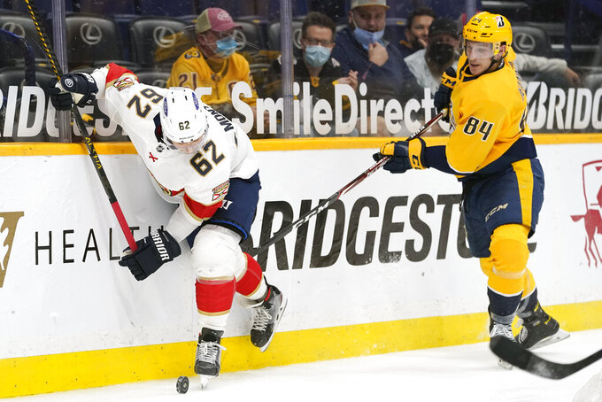 Florida Panthers defenseman Brandon Montour (62) and Nashville Predators left wing Tanner Jeannot (84) battle for the puck in the second period of an NHL hockey game Tuesday, April 27, 2021, in Nashville, Tenn. (AP Photo/Mark Humphrey)
