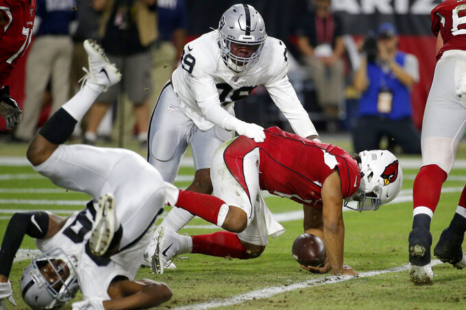 Arizona Cardinals quarterback Kyler Murray (1) is tackled in the end zone for a safety by by Oakland Raiders free safety Lamarcus Joyner, left, as defensive end Arden Key (99) pursues during the first half of an an NFL football game, Thursday, Aug. 15, 2019, in Glendale, Ariz. (AP Photo/Rick Scuteri)