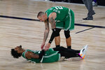 Boston Celtics guard Marcus Smart (36) lis assisted by center Daniel Theis (27) after he was injured during the second half of an NBA conference semifinal playoff basketball game against the Toronto Raptors Wednesday, Sept. 9, 2020, in Lake Buena Vista, Fla. (AP Photo/Mark J. Terrill)