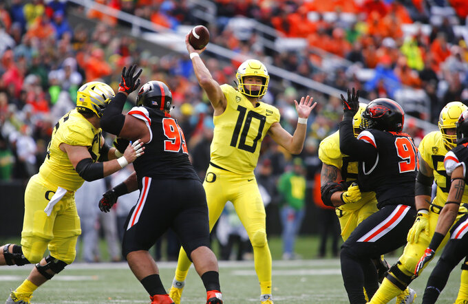Oregon quarterback Justin Herbert throws a pass against Oregon State during the first half of an NCAA college football game in Corvallis, Ore., Friday, Nov. 23, 2018. (AP Photo/Timothy J. Gonzalez)