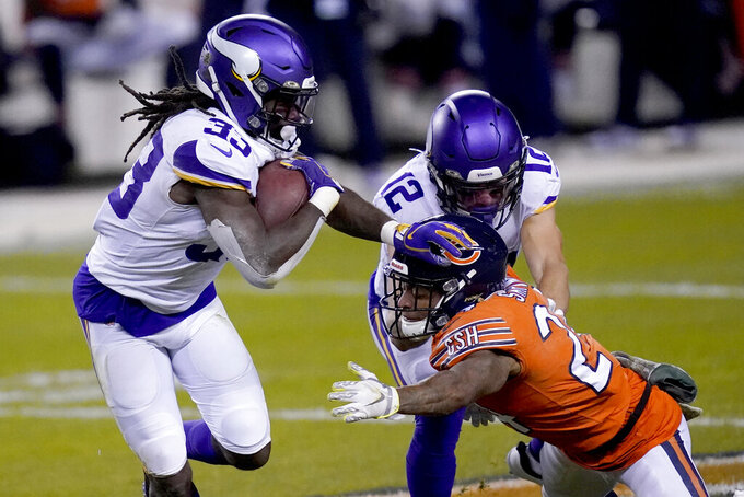 Minnesota Vikings running back Dalvin Cook (33) runs past teammate Chad Beebe (12) as Chicago Bears cornerback Buster Skrine, front right, defends during the first half of an NFL football game Monday, Nov. 16, 2020, in Chicago. (AP Photo/Charles Rex Arbogast)