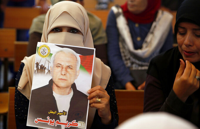 FILE - In this Oct. 28, 2019, file photo, a Palestinian woman holds a portrait of a relative being held in an Israeli jail as they demonstrate for prisoner release, in front of the International Committee of the Red Cross, in Gaza City. Palestinian officials said Friday, May 8, 2020 that Israel is forcing banks in the occupied West Bank to close accounts held by the families of prisoners in Israeli jails to prevent the Palestinian Authority from providing stipends to them.(AP Photo/ Hatem Moussa, File)