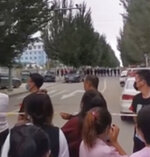 In this image made from video taken in August 2020, parents gather behind a police line outside a school in Tongliao in Northwestern China's Inner Mongolia region. Ethnic Mongolians, including students and parents, in China's Inner Mongolia region are demonstrating their anger in rare public protests against a new bilingual education policy that they say is endangering the Mongolian language. (AP Photo)