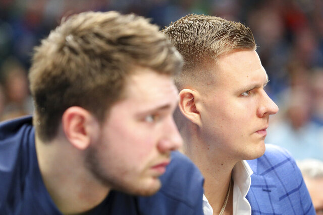 Dallas Mavericks forward Luka Doncic, left, and forward Kristaps Porzingis sit on the bench during the first half of the team's NBA basketball game against the Los Angeles Lakers on Friday, Jan. 10, 2020, in Dallas. (AP Photo/Richard W. Rodriguez)