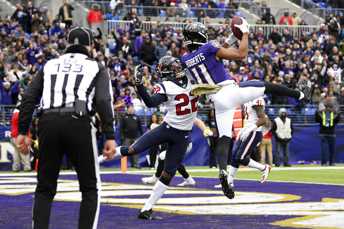 Baltimore Ravens wide receiver Seth Roberts (11) catches a touchdown pass from quarterback Lamar Jackson, not visible, as Houston Texans cornerback Gareon Conley (22) tries to stop him during the first half of an NFL football game, Sunday, Nov. 17, 2019, in Baltimore. (AP Photo/Nick Wass)