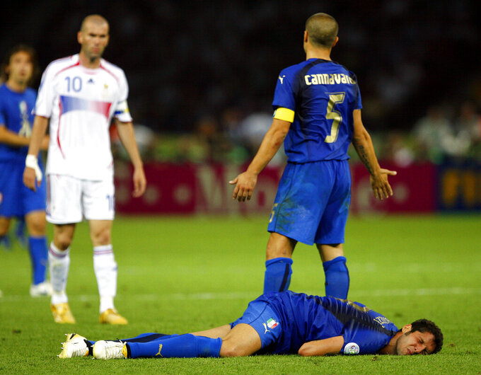 FILE - France's Zinedine Zidane, left, looks on after head butting Italy's Marco Materazzi in the chest as Italy's Fabio Cannavaro reacts during extra time in the final of the soccer World Cup soccer match at the Olympic Stadium in Berlin. Violence is part of the game in many sports. But when the Cleveland's Myles Garrett ripped the helmet off Mason Rudolph and hit the Pittsburgh Steelers' quarterback in the head with it, the Browns' defender crossed a line _ one that attracts the attention of authorities sometimes from within their sport and in other cases from criminal prosecutors. (AP Photo/Jasper Juinen, File)