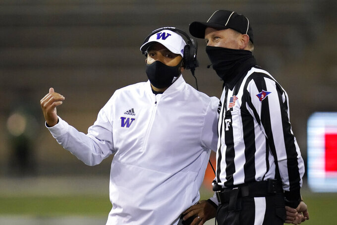 Washington coach Jimmy Lake talks with field judge Todd Migchelbrink during the first half of an NCAA college football game Saturday, Nov. 21, 2020, in Seattle. (AP Photo/Elaine Thompson)