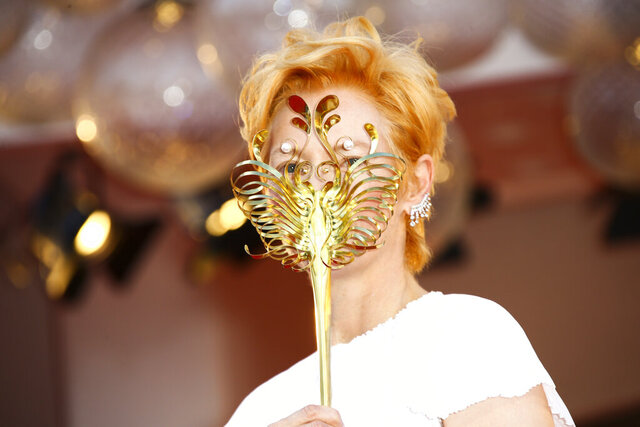 Actress Tilda Swinton holds a carnival mask as she poses for photographers upon arrival at the opening ceremony of the 77th edition of the Venice Film Festival in Venice, Italy, Wednesday, Sept. 2, 2020. (Photo by Joel C Ryan/Invision/AP)