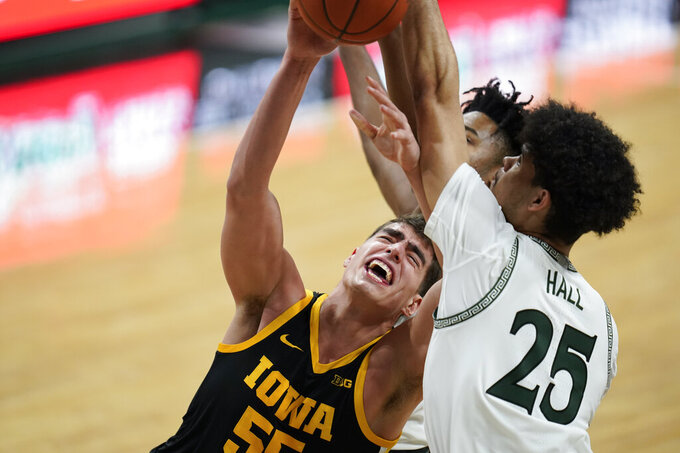 Iowa center Luka Garza (55) is defended by Michigan State forward Malik Hall (25) in the first half of an NCAA college basketball game in East Lansing, Mich., Saturday, Feb. 13, 2021. (AP Photo/Paul Sancya)