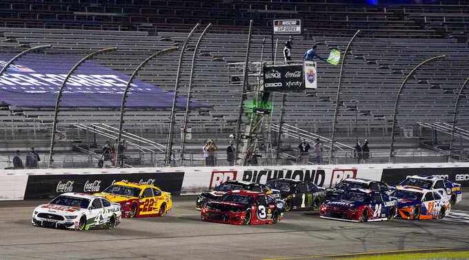Defense Secretary Mark Esper waves the green flag as Kevin Harvick (4) leads the field at the start of the NASCAR Cup Series auto race Saturday, Sept. 12, 2020, in Richmond, Va. (AP Photo/Steve Helber)