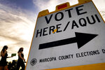 FILE - In this Nov. 3, 2020, file photo voters deliver their ballot to a polling station in Tempe, Ariz. Arizona and Texas are both in the final stages of work on contentious pieces of state legislation to tighten voting laws. The GOP has pushed these measures after former President Donald Trump's false insistence that he only lost the 2020 election because of voter fraud. (AP Photo/Matt York, File)