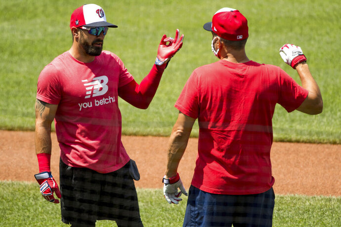 Washington Nationals' Adam Eaton (2), left, speaks with a staff member as the Washington Nationals hold their first training camp work out at Nationals Stadium, Friday, July 3, 2020, in Washington. (AP Photo/Andrew Harnik)