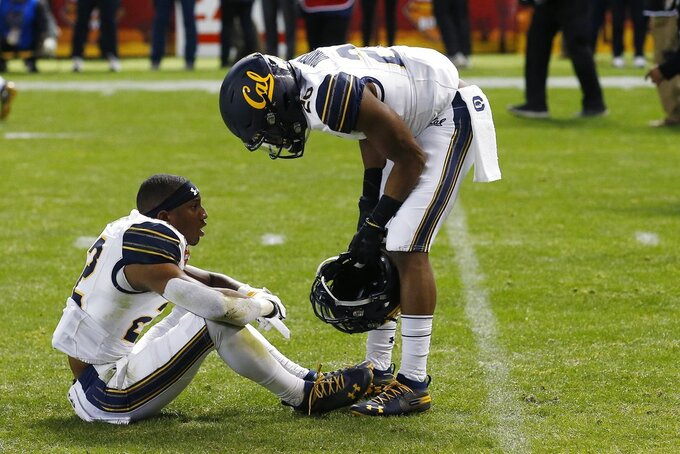 California's Traveon Beck, left, is consoled by Josh Drayden (20) after a TCU game-winning field goal in overtime of the Cheez-It Bowl NCAA college football game Wednesday, Dec. 26, 2018, in Phoenix. TCU defeated California 10-7. (AP Photo/Ross D. Franklin)