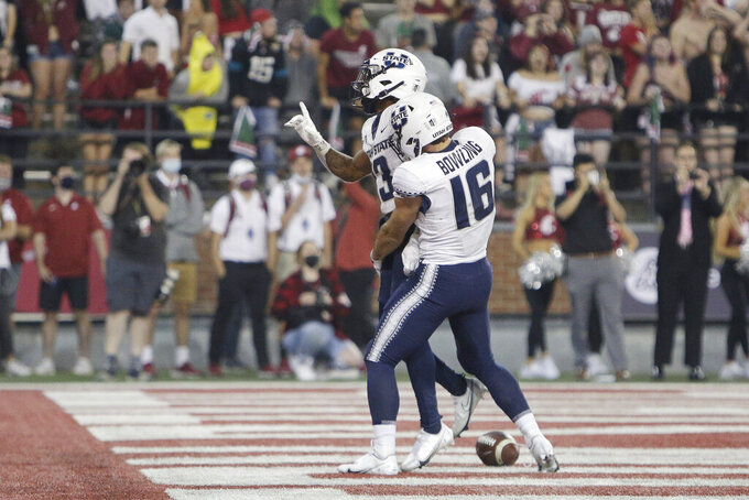 Utah State wide receiver Deven Thompkins, left, celebrates his touchdown with wide receiver Brandon Bowling during the second half of an NCAA college football game against Washington State, Saturday, Sept. 4, 2021, in Pullman, Wash. Utah State won 26-23. (AP Photo/Young Kwak)