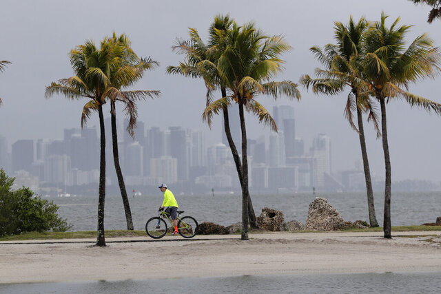 The Miami skyline is shrouded in clouds as a cyclist rides along Biscayne Bay at Matheson Hammock Park, Friday, May 15, 2020, in Miami. A trough of low pressure moving through the Florida Straits could organize over the northwest Bahamas later Friday or Saturday and become the first named storm of the 2020 hurricane season, the U.S. National Hurricane Center in Miami said. (AP Photo/Lynne Sladky)