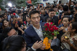 Thanathorn Juangroongruangkit, center, leader of the anti-military Future Forward Party is surrounded by his supporters as he arrives at Constitutional Court in Bangkok, Thailand, Wednesday, Nov. 20, 2019.  Thanathorn is expected to receive a verdict whether he is eligible to remain as a member of the parliament due to an accusation of owning media shares a violation of the Thai constitution. (AP Photo/Gemunu Amarasinghe)