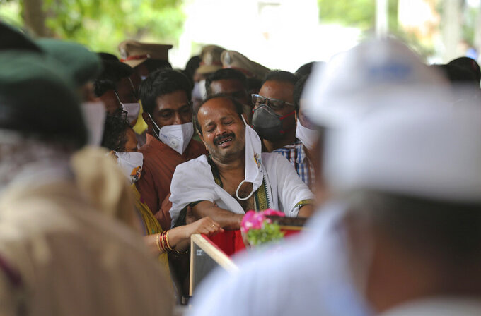FILE - In this Thursday, June 18, 2020, file photo, B. Upender weeps by the coffin of his son Colonel B. Santosh Babu, who was among the twenty Indian troops killed in a clash with Chinese soldiers in Galwan Valley, in Suryapet, about 140 kilometers from Hyderabad, India. As the escalating and bitter military standoff between India and China protracts following their bloodiest confrontation in decades in the Ladakh region in 2020, experts warn the two nuclear-armed countries can unintentionally slide into a war over the roof of the world. About four months after the standoff began when rival soldiers brawled bitterly in May, and then in June fought in medieval fashion with clubs, stones and their fists, leaving 20 Indian soldiers dead and dozens wounded, an apparent tit-for-tat military actions have fueled a war of harsh words between Beijing and New Delhi. (AP Photo/Mahesh Kumar A., File)