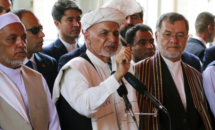 Afghanistan's President Ashraf Ghani, center, speaks after offering Eid al-Adha prayers at the presidential palace in Kabul, Afghanistan, Sunday, Aug. 11, 2019. Ghani is urging the nation to determine its fate without foreign interference as the United States and the Taliban appear to near a peace deal without the Afghan government at the table.(AP Photo/Nishanuddin Khan)