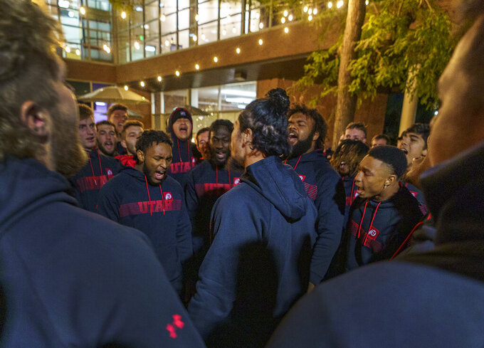 Members of the University of Utah football team mourn the loss of fellow student-athlete Aaron Lowe during a candlelight vigil on the southwest lawn of the university's student union, Wednesday, Sept. 29, 2021, in Salt Lake City. Lowe was fatally shot at a house party early Sunday, Sept. 26. (Leah Hogsten/The Salt Lake Tribune via AP)