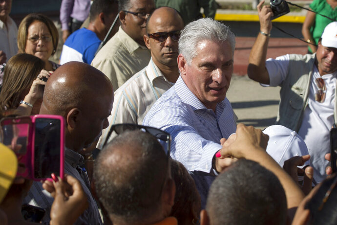 Cuba's President Miguel Diaz-Canel greets residents as he arrives in Caimanera, Cuba, Thursday, Nov. 14, 2019.  Díaz-Canel is making his first trip to the town of Caimanera, the closest point in Cuba to the U.S. naval base at Guantanamo Bay. He arrived on Thursday morning. ( AP Photo/Ismael Francisco)