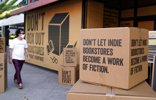 FILE - A pedestrian walks past boxes set up in front of book store Book Soup in West Hollywood, Calif., on Oct. 16, 2020, to encourage shoppers to buy from independent book stores instead of online retailers like Amazon. For independent stores and publishers, the pandemic amplified the divide between the industry's biggest players and everyone else. (AP Photo/Chris Pizzello, File)