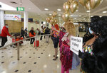 Passengers from New Zealand are welcomed by drag queens as they arrive at Sydney Airport in Sydney, Australia, Monday, April 19, 2021, as the much-anticipated travel bubble between Australia and New Zealand opens. (AP Photo/Rick Rycroft)