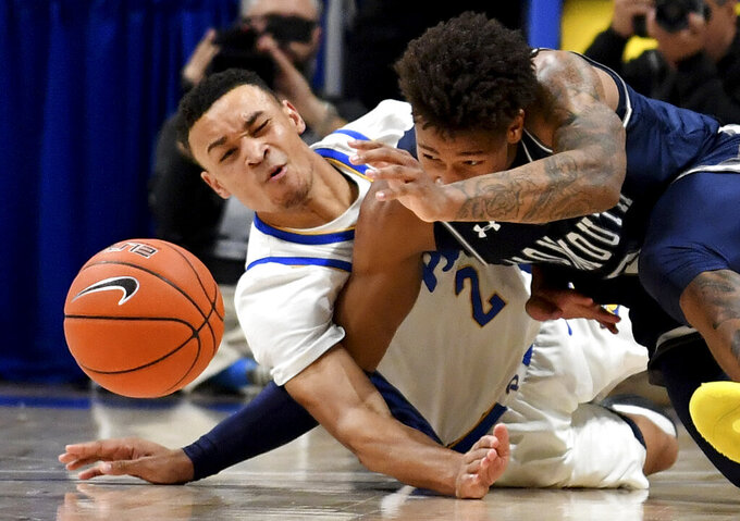Pitt guard Trey McGowens gets tangled up with Monmouth guard Deion Hammond as they dive for a loose ball in the second half  of an NCAA college basketball game Monday, Nov. 18, 2019, in Pittsburgh, Pa. (Matt Freed/Pittsburgh Post-Gazette via AP)