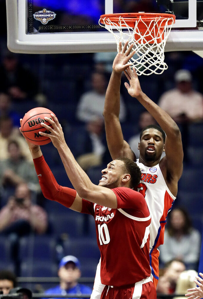 Arkansas forward Daniel Gafford (10) pulls in a rebound in front of Florida center Kevarrius Hayes (13) in the second half of an NCAA college basketball game at the Southeastern Conference tournament Thursday, March 14, 2019, in Nashville, Tenn. Florida won 66-50. (AP Photo/Mark Humphrey)
