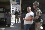 Lebanese army soldiers arrest an anti-government protester after scuffles broke out in the town of Zouk Mosbeh, north of Beirut, Lebanon, Tuesday, Nov. 5, 2019. Lebanese troops deployed in different parts of the country Tuesday reopening roads and main thoroughfares closed by anti-government protesters facing resistance in some areas that led to scuffles. (AP Photo/Hassan Ammar)