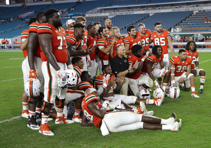 Miami head coach Mark Richt poses with the seniors after an NCAA college football game against Pittsburgh, Saturday, Nov. 24, 2018, in Miami Gardens, Fla. Miami won 24-3. (AP Photo/Lynne Sladky)