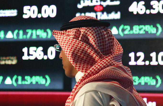 FILE - In this June 15, 2015, file photo, a Saudi man walks through the Tadawul stock exchange in Riyadh, Saudi Arabia. Saudi Arabia's National Commercial Bank said Sunday, Oct. 11, 2020, it will purchase rival lender Samba Financial Group in a deal valued at $14.8 billion, creating what would become the kingdom's largest bank. (AP Photo/Hasan Jamali, File)