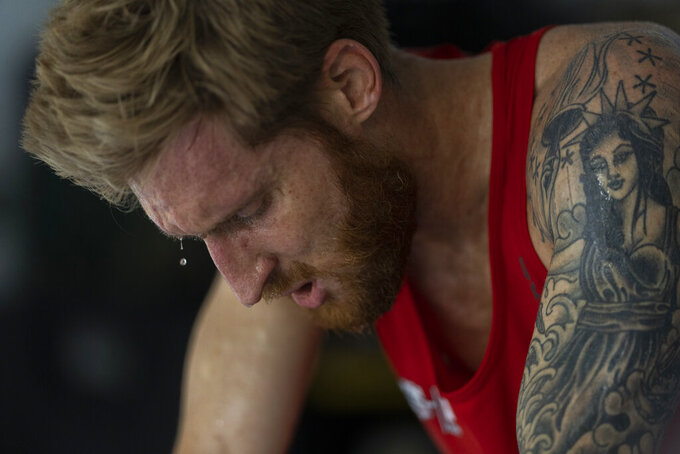 Brad Snyder works out on his stationary bicycle during daily training in his garage in Princeton, N.J., on Thursday, Aug. 5, 2021. A top swimmer at the U.S. Naval Academy, Snyder won his first two Paralympic gold medals in London barely a year after losing his sight. He won three more in Rio De Janeiro in 2016, then switched to the triathlon. (AP Photo/Emilio Morenatti)