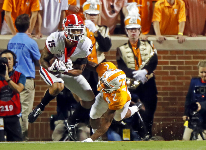 Georgia wide receiver Lawrence Cager (15) catches a pass for a touchdown in front of Tennessee defensive back Alontae Taylor (2) in the first half of an NCAA college football game, Saturday, Oct. 5, 2019, in Knoxville, Tenn. (AP Photo/Wade Payne)